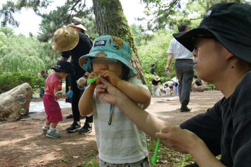 幼児教室の2歳児が、息を上手に吹いて丸いシャボン玉を作りました。