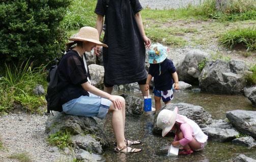 未就園児・母子分離クラスの生徒がお母様といっしょに京都御苑の出水の小川で、手作りのシャワーを使って水遊びをしています。