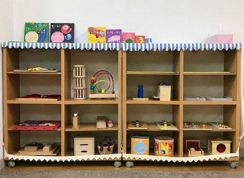 ハイハイやつかまり立ちができるようになった0歳児のお子様に向けて、いろいろな教具を置いた2つの棚を設けた個別活動のスペースを用意しました。