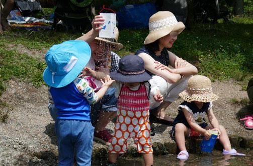 未就園児・親子クラス(6ヶ月~2歳)の1歳児が、手作りのシャワーで水遊びをしています。