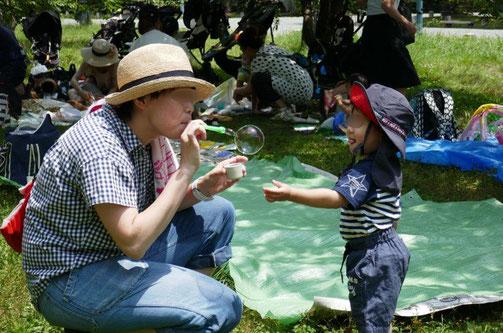 京都の幼児教室が京都御苑の出水の小川で水遊び。あかあさんがシャボン玉を吹いているのを子供が楽しそうに見ています。