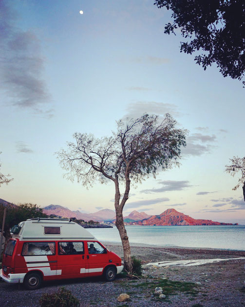 Roter VW Bus steht bei Abenddämmerung am Strand mit Blick auf Meer und Berge