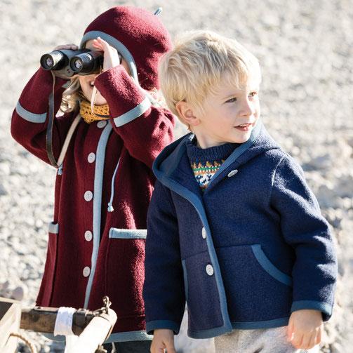 ein mädchen in einem roten walk kindermantel mit walkmütze schaut durchs fernglas und daneben steht ein junge in einer warmen jacke aus blauem walk aus merinowolle. die kleidung wird nachhaltig produziert.