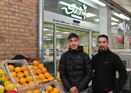 Inhaber und Azubi stehen vor dem Laden
