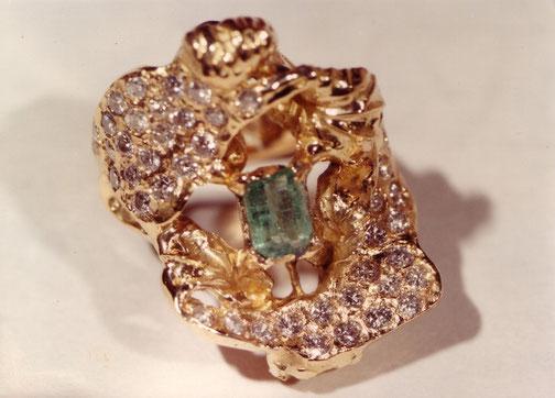 Une bague de haute-joaillerie composées de diamants et d'émeraude est exposée sur fond blanc.