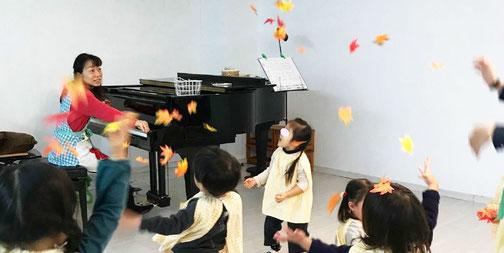 2歳児のリトミックで落ち葉を使ったレッスン ピアノに合わせて床の落ち葉を宙に投げます