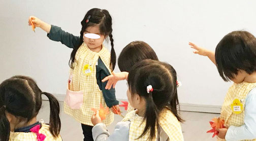 フィオーレコース(2歳児) リトミックでトライアングルの鳴る音に合わせて落ち葉を1枚ずつ落とします
