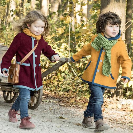 zwei kinder in einem roten walkmantel und einer gelben walkjacke aus merinowolle ziehen einen bollerwagen. kuschelig warm eingepackt in naturfasern