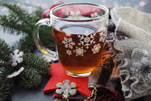 A glass of hot tea with snow flake decoration
