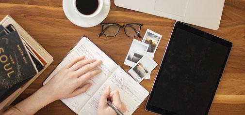 手帳やiPadなどに仕事のメモをまとめる様子