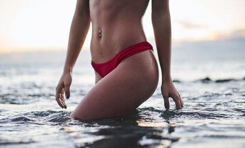 schlanke Frau in rotem Bikini läuft aus dem Wasser