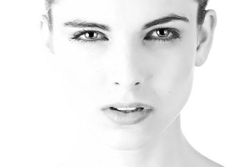 Frau mit glatter Gesichtshaut schaut in Kamera - schwarz-weiß