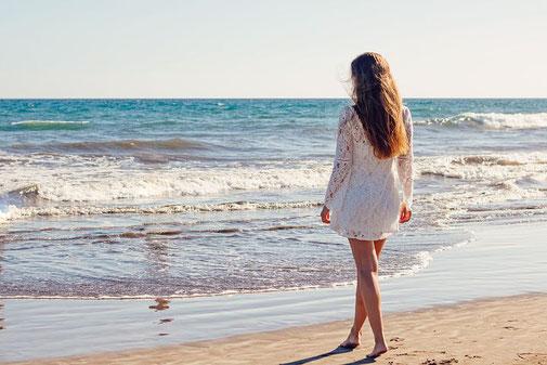 Blonde Frau in weißem Kleid läuft ins Meer