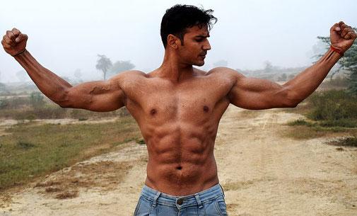 Dunkelhaariger Mann mit muskulösem nackten Oberkörper