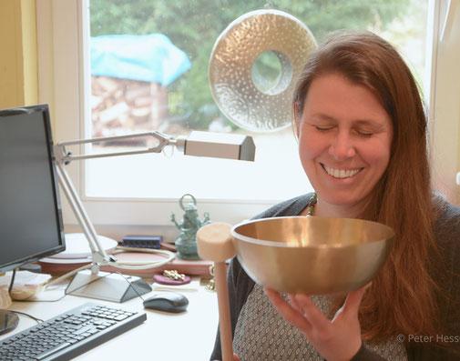 Frau mit Klangschale am Schreibtisch genießt den Klang