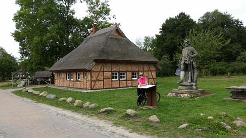 Das Verräterhaus hinter der Statue von König Fridrich Wilhelm I. Sie stand ursprünglich am Ortsrand von Groß-Stresow.