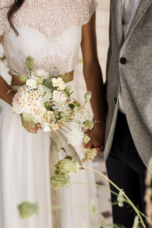 Brautpaar das Händchen hält zweiteiliges Brautkleid, weiß-grüner Brautstrauß