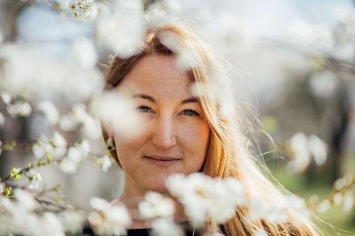 Hochzeitsplanerin Katharina Gronwald-Stolte Portrait hinter blühenden Zweigen