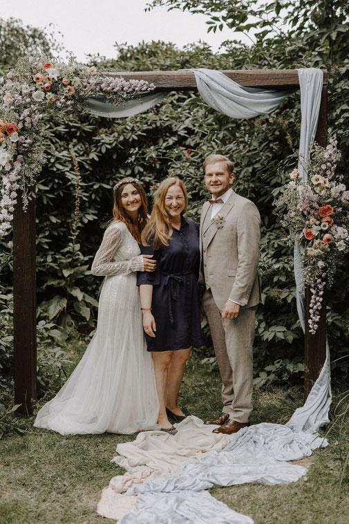Brautpaar mit Weddingplaner Katharina Gronwald Stolte unter geschmücktem Traubogen
