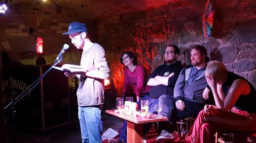Die Mitglieder der Lesebühne Kunstloses Brot bei ihrer Lesung im Beyerhaus. Am Mikro steht David Weber. Sarah Teicher, Nils Matzka, Jan Lindner und Louise Kenn sitzen dahinter auf Stühlen und hören amüsiert zu.