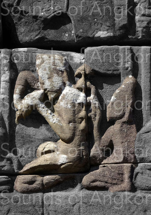 The left character blows into a conch while the one behind him hits a bell tree with five bells. Bayon. Exterior east gallery.