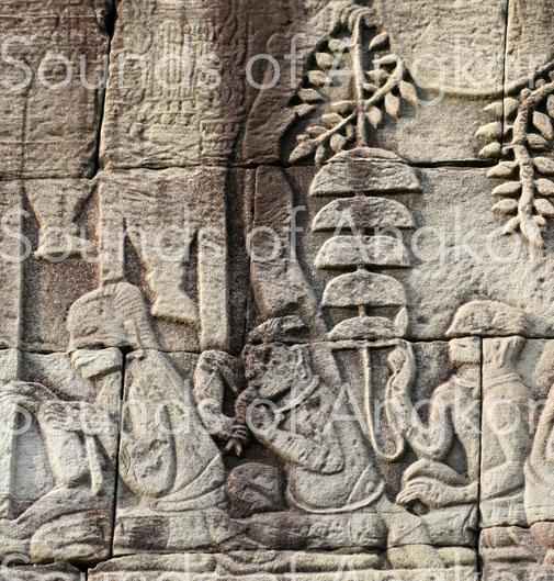 The second character from the left blows into a conch while the one behind him hits a bell tree with five bells. Bayon. Exterior gallery south.