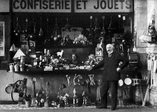 Méliès avec sa nouvelle femme, Jehanne d'Alcy (une de ses anciennes actrices), qu'il épouse en 1925, devant sa boutique de confiseries/jouets à la gare Montparnasse à Paris.