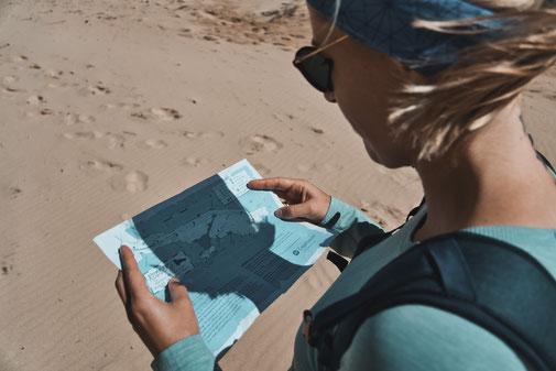 Blonde Frau schaut sich am Strand eine Wanderkarte an