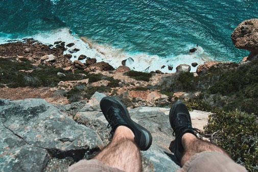 Mann sitzt auf einer Steinklippe und schaut in den Abgrund aufs Meer