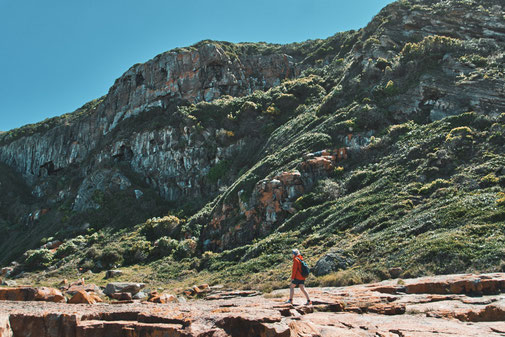 Frau in roter Jacke läuft Felsigen Strand entlang, vorbei an grün bewachsenen Bergen