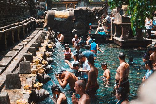 Tirtam Empul in Bali. Menschen baden in heiligem Wasser