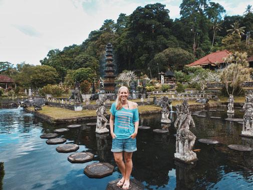 Frau steht auf Steinen im Teich im Wassertempel Tirtagangga. Ringsherum Statuen, im Hintergrund ein großer Brunnen.