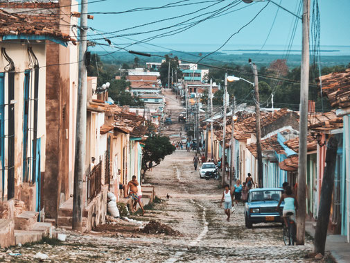 Eine gepflasterte Straße von einen Hügel hinab. Am Rand Menschen und Autos. Mitten in Trinidad Kuba.