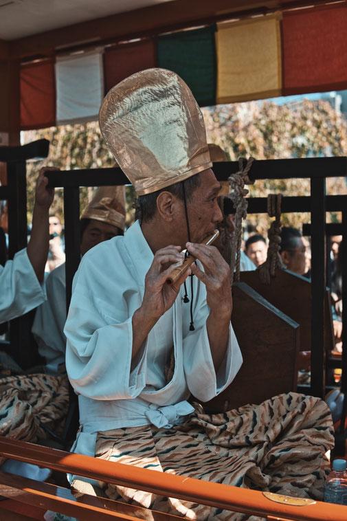 Ein Japaner mit goldenem Hut spielt Blockflötte