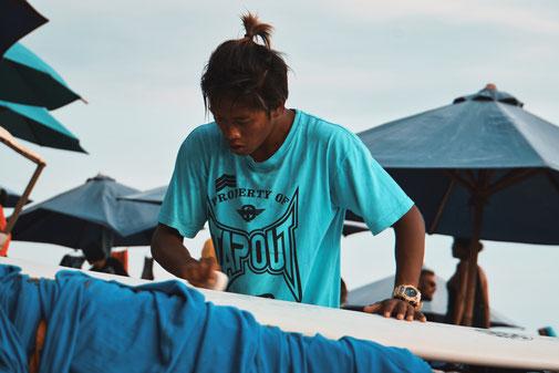 Balinese waxt sein Surfboard am Strand