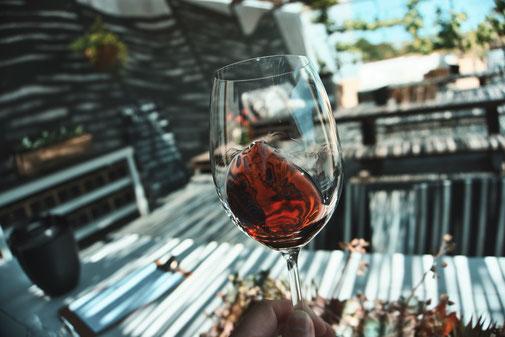 Ein Glas Rotwein wird geschwenkt