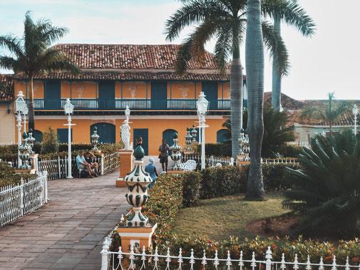 Marktplatz in Trinidad Kuba. Alte Kolonialbauten umgeben von Palmen.