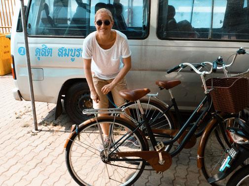 Blonde Frau schließt Fahrrad in Thailand ab
