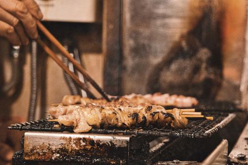 Fleischspiesse auf einem Grill werden mit Stäbchen gewendet