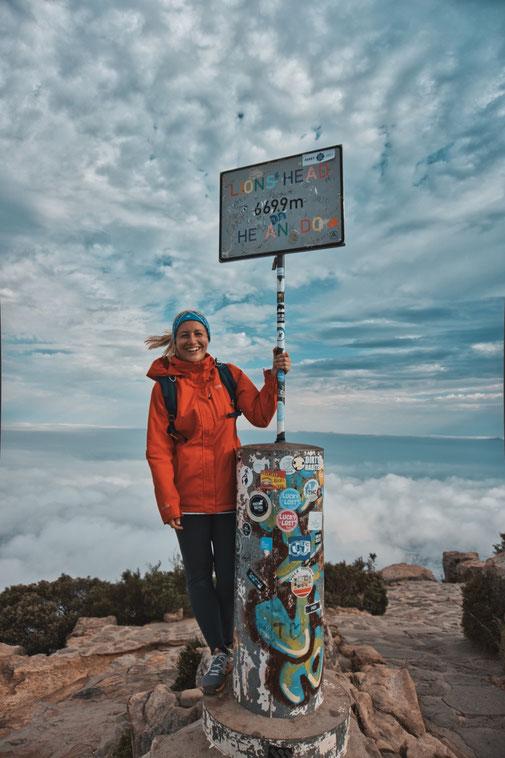 Blonde Frau steht an einem Schild des Gipfels vom Lions Head
