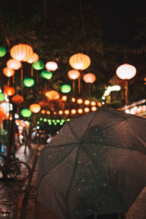 Frau mit Regenschirm steht unter Lampions in Hoi an