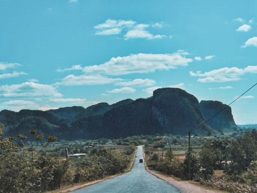 Straße führt in Vinales Tal, umgeben von Bergen.