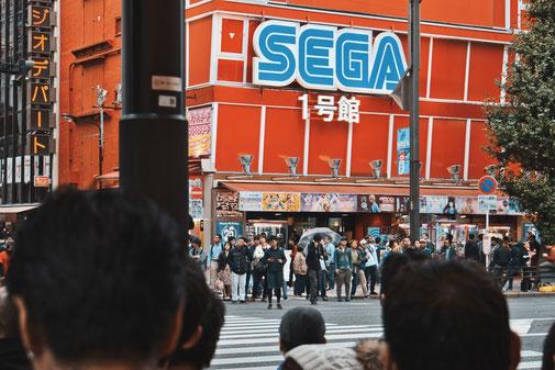 Riesige WErbeanzeige von Sega auf Häuserwand in Tokio an einer Kreuzung