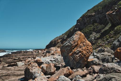 Großer Stein an Klippe, im Hintergrund das Meer