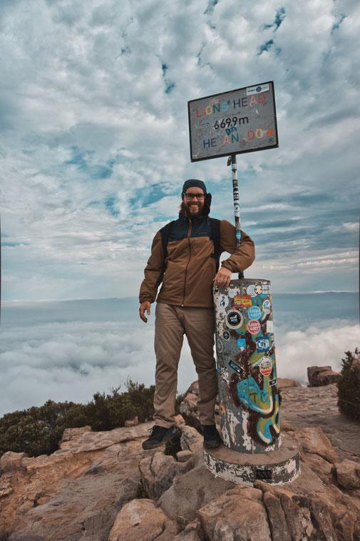 Mann steht an einem Schild des Gipfels vom Lions Head