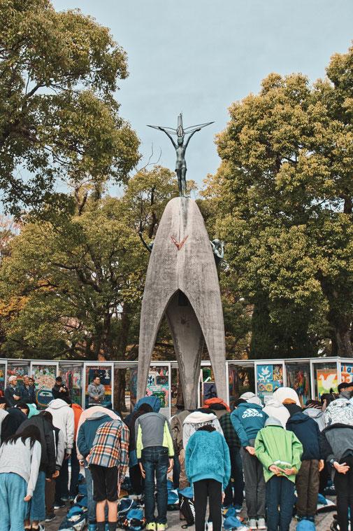 Kinder Friedensdenkmal in Hiroshima. Sadako Sasaki Statur mit Kranich. Eine Schulklasse verbeugt sich