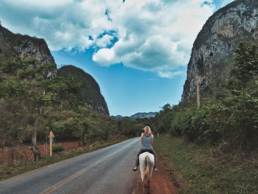 Frau reitet auf einem weißem Pferd durch bergiges Tal in Vinales, Kuba.
