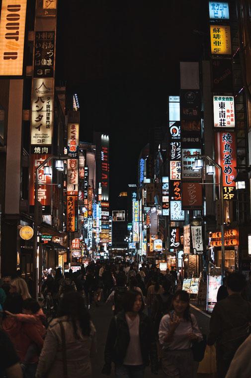 Strasse in Tokio mit unmengen blinkender und leuchtender werbetafeln