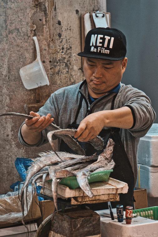 Fischhändler wiegt seinen Fisch ab