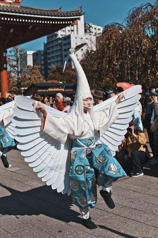 Eine als Kranich verkleidetet Japanerin